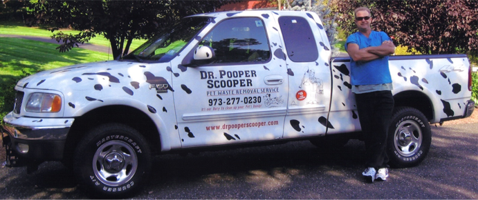 Owner Richard Roy standing next to his white Dr Pooper Scooper Truck